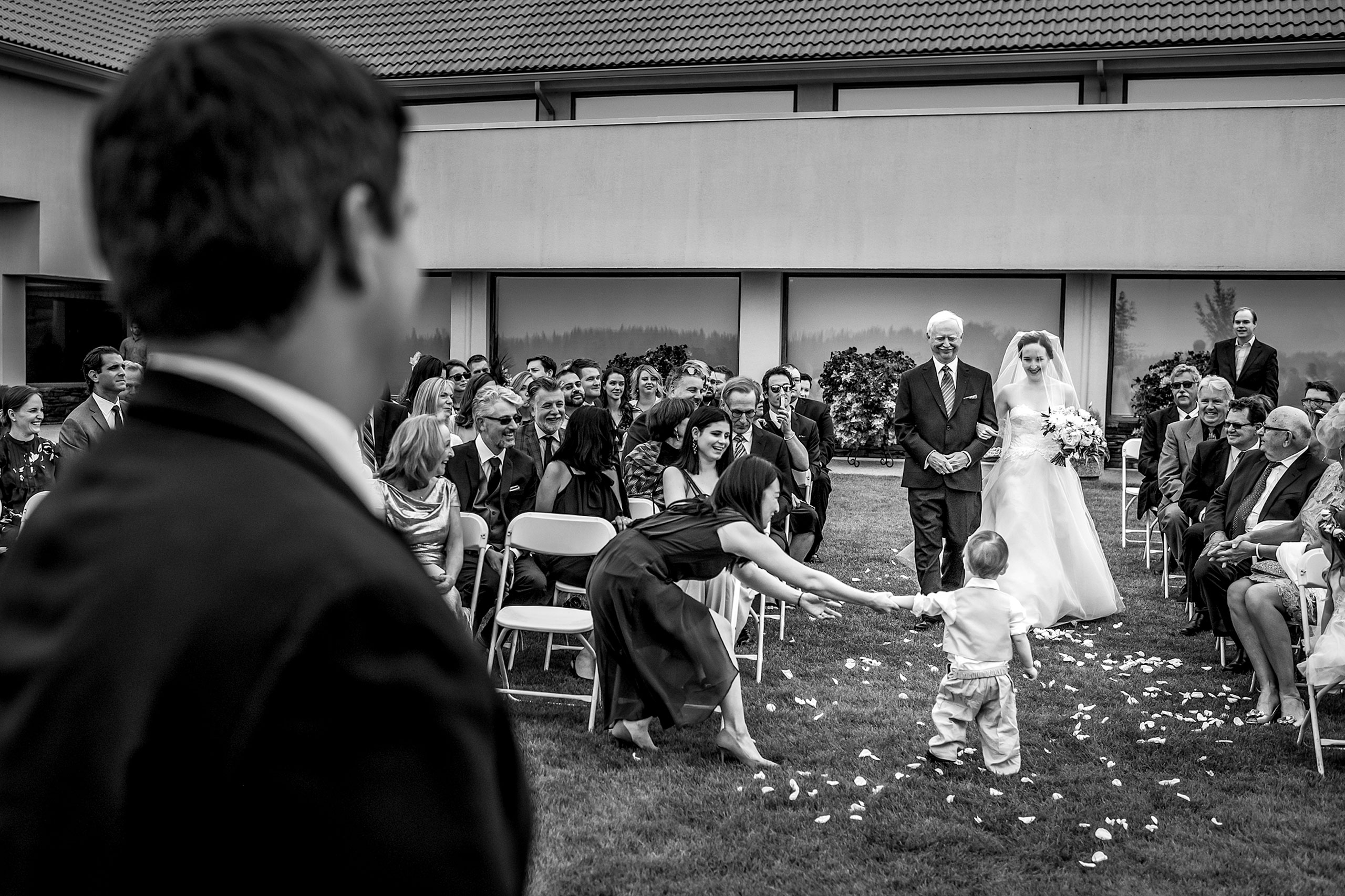 a bride and her dad walking down the aisle at a wedding ceremony and a little boy stopped in the aisle by award winning photographer sean leblanc