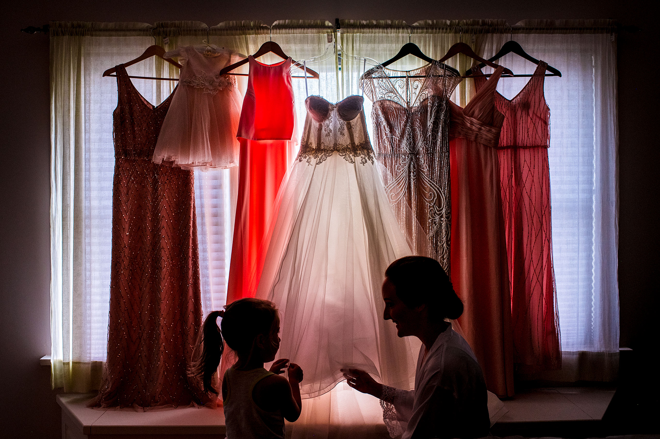 a bride showing a flower girl her wedding dress in front of a window by calgary wedding photographer sean leblanc
