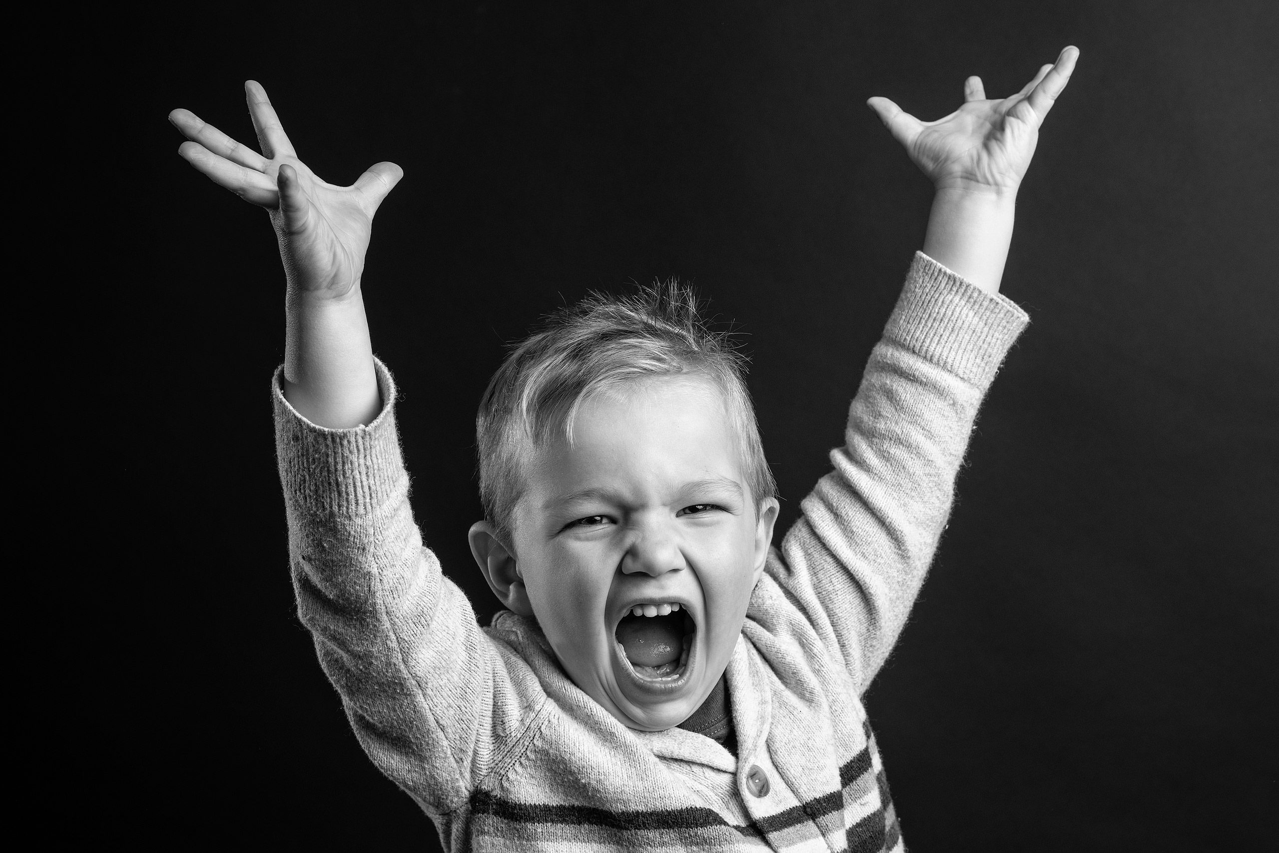 young boy lifting his hands in the air in studio taken by family photographer sean leblanc