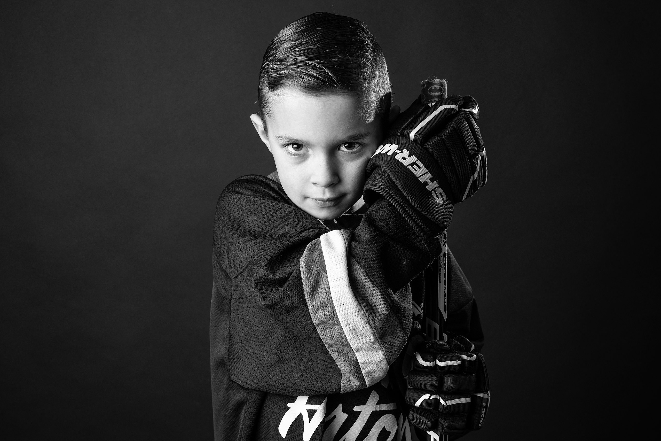 young boy posing with his hockey stick taken by family photographer sean leblanc