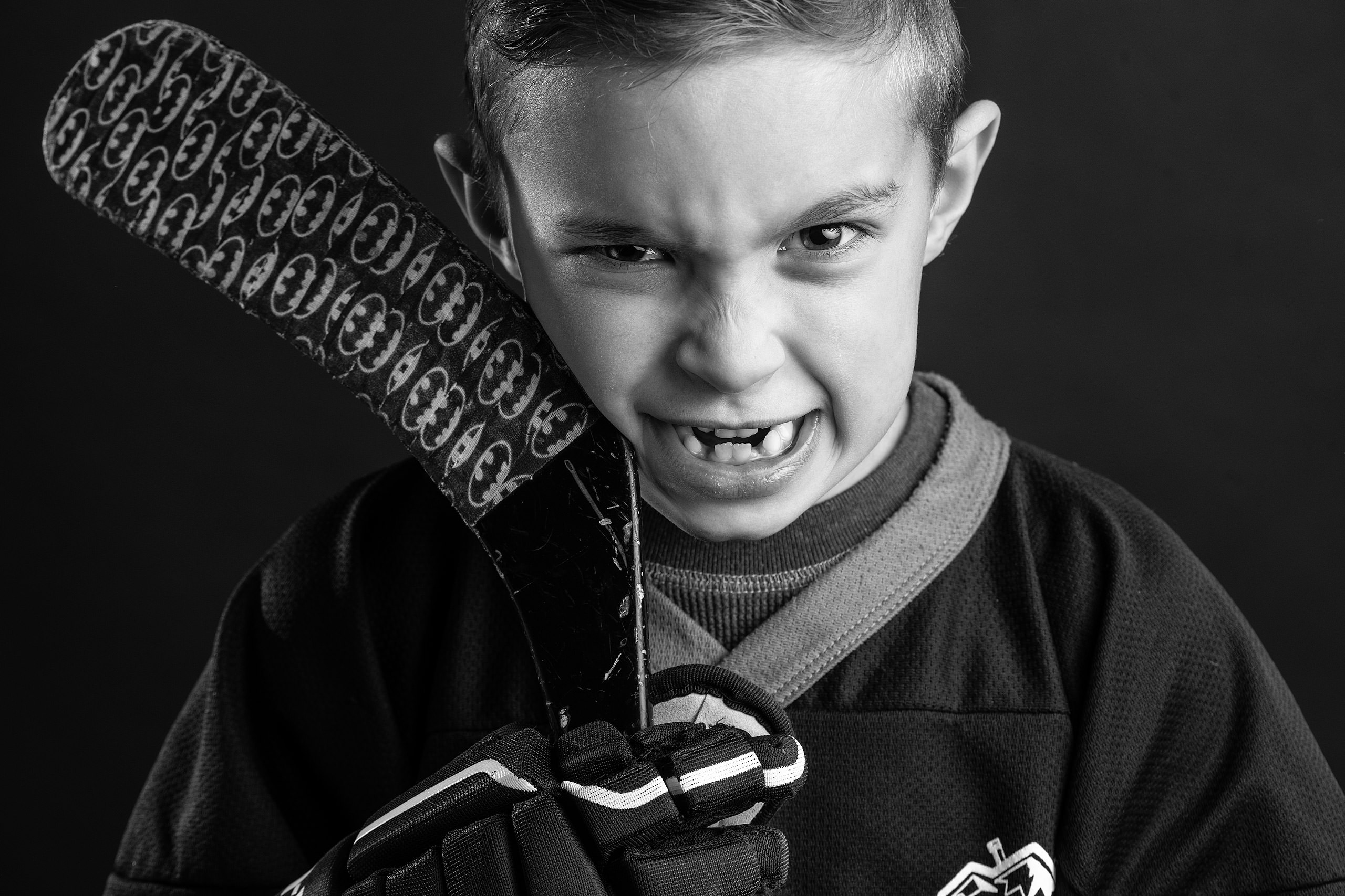young both making a mean face with his hockey stick taken by family photographer sean leblanc
