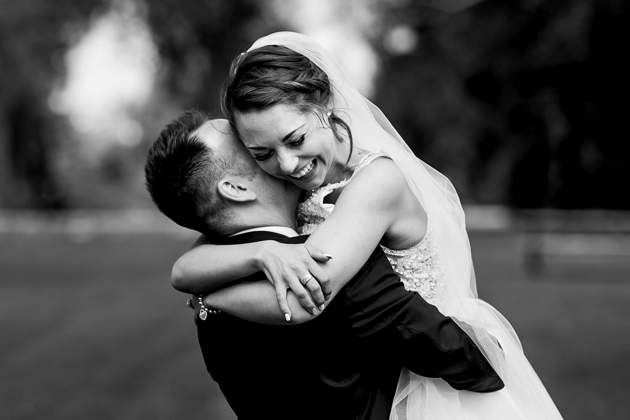 bride and groom embracing in the park by calgary wedding photographer sean leblanc