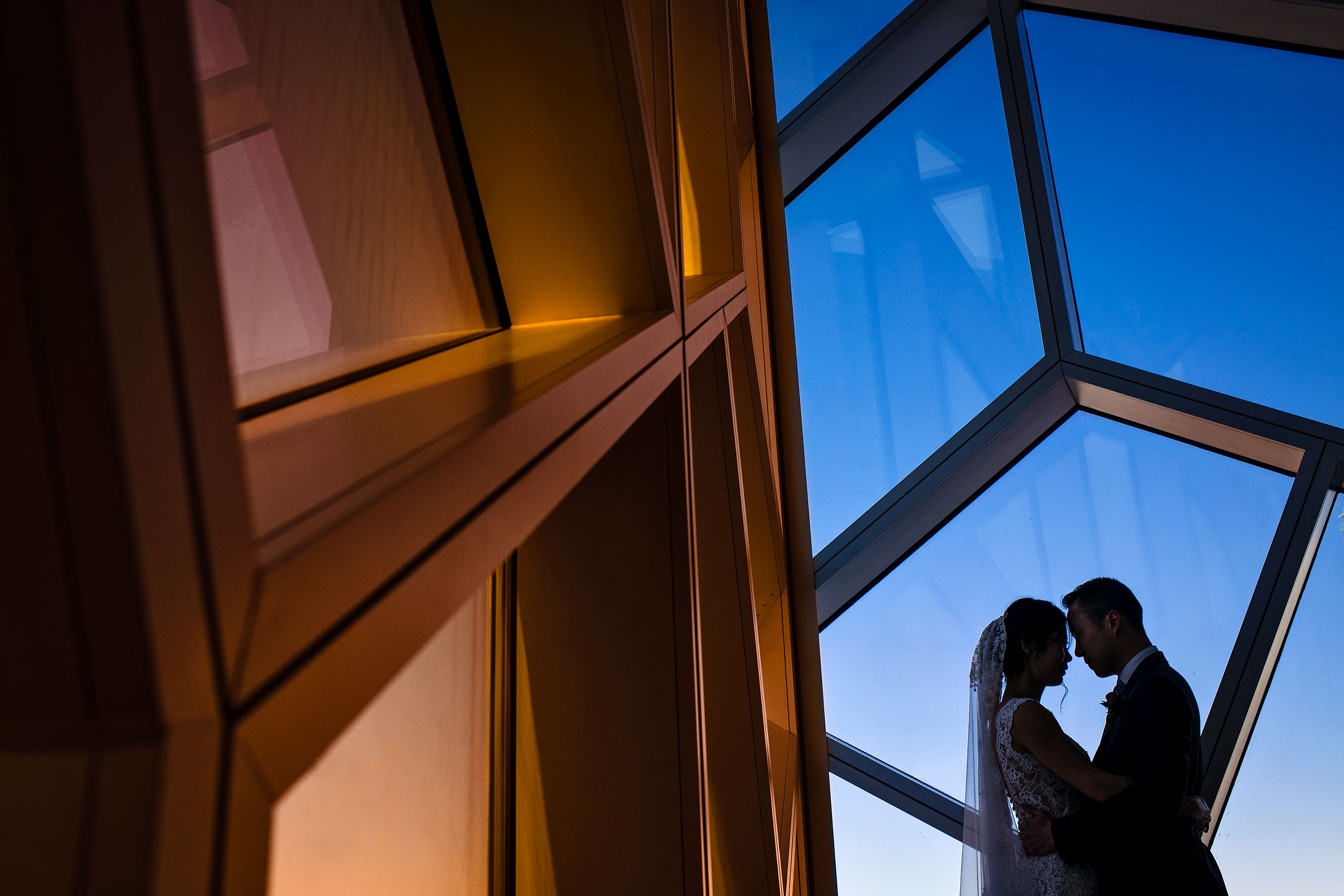 a bride and groom standing by a window at the calgary library for their calgary lake house wedding by calgary wedding photographer sean leblanc photography