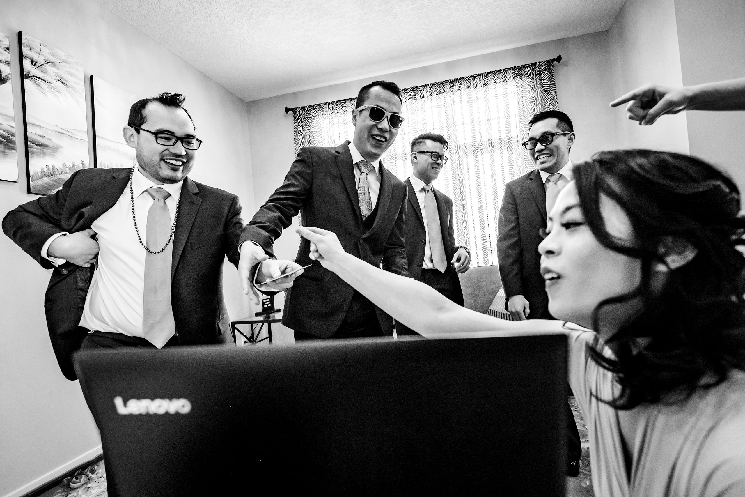 groomsmen laughing in at a computer screen at a calgary lake house wedding by calgary wedding photographer sean leblanc photography