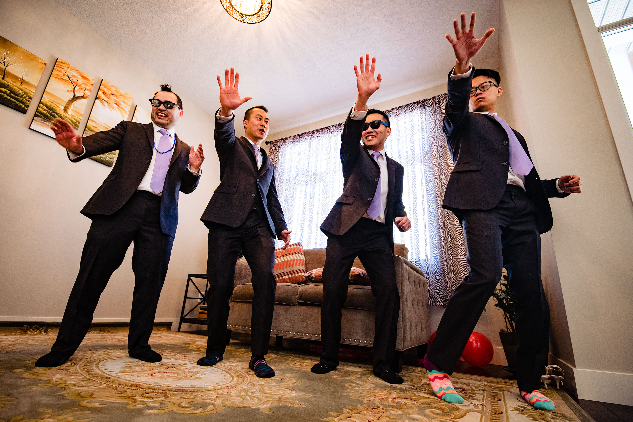 four groomsmen dancing to bruno mars at a calgary lake house wedding by calgary wedding photographer sean leblanc photography