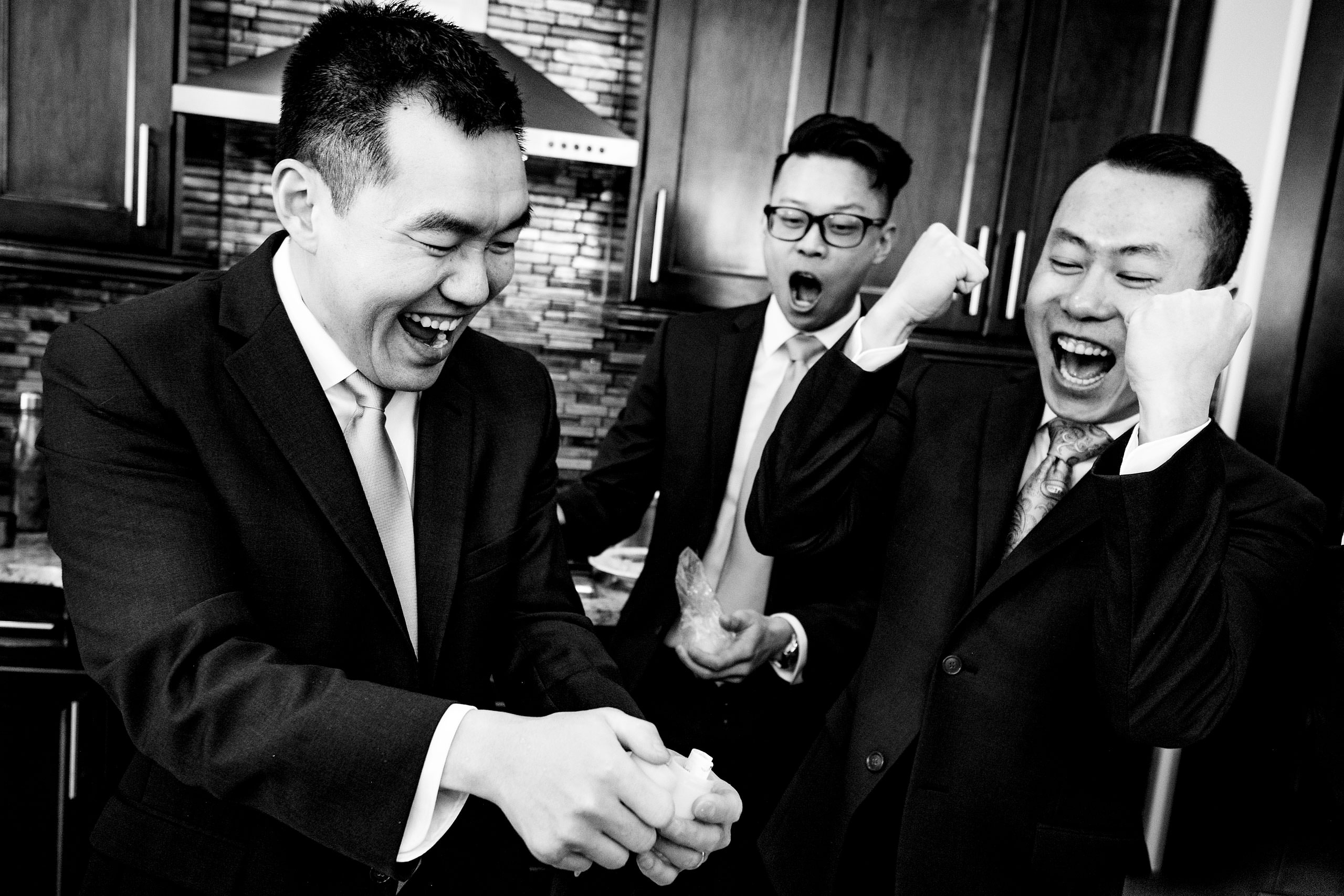 three groomsmen cheering at a piece of paper at a calgary lake house wedding by calgary wedding photographer sean leblanc photography