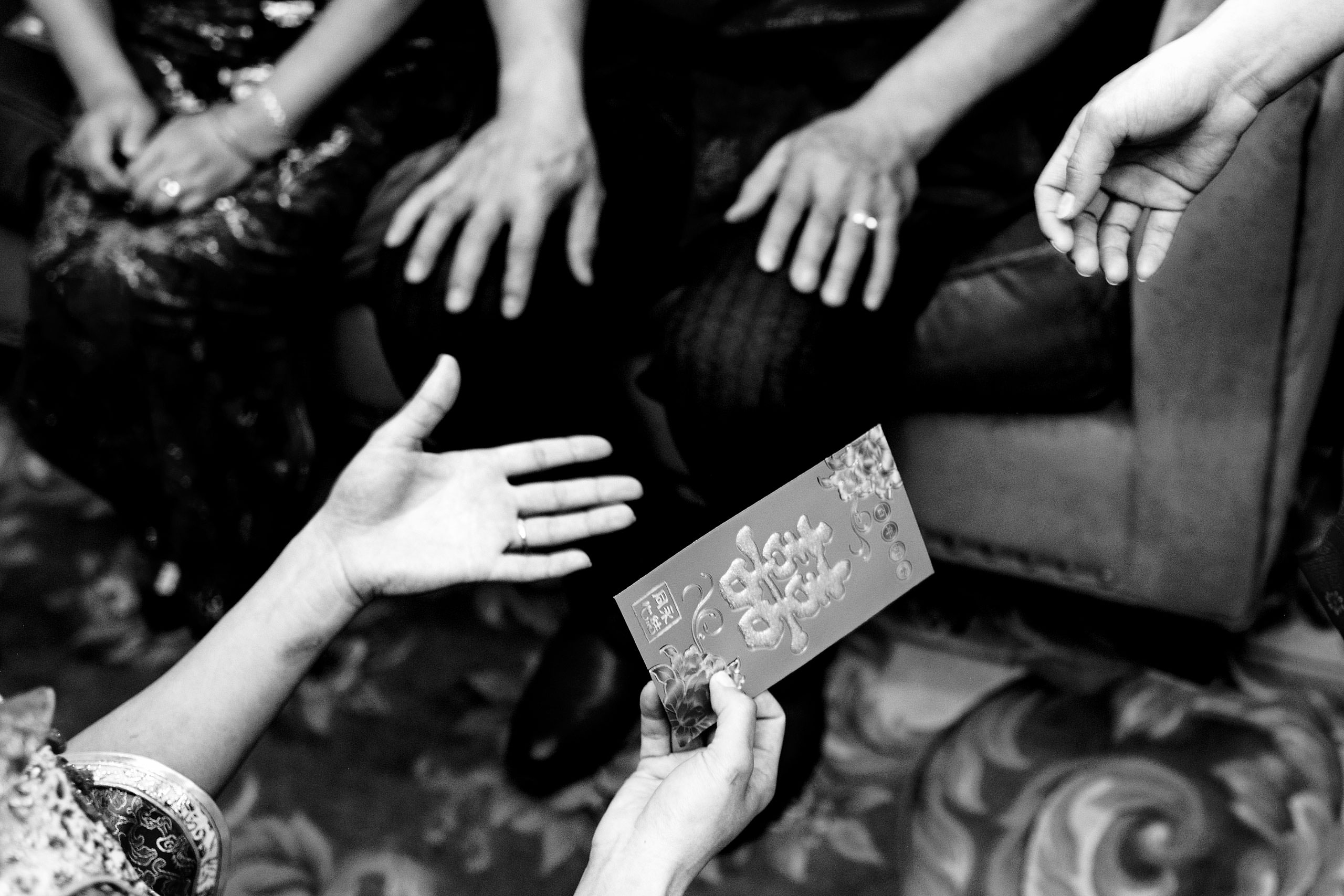 hands exchanging a gift at a calgary lake house wedding by calgary wedding photographer sean leblanc photography