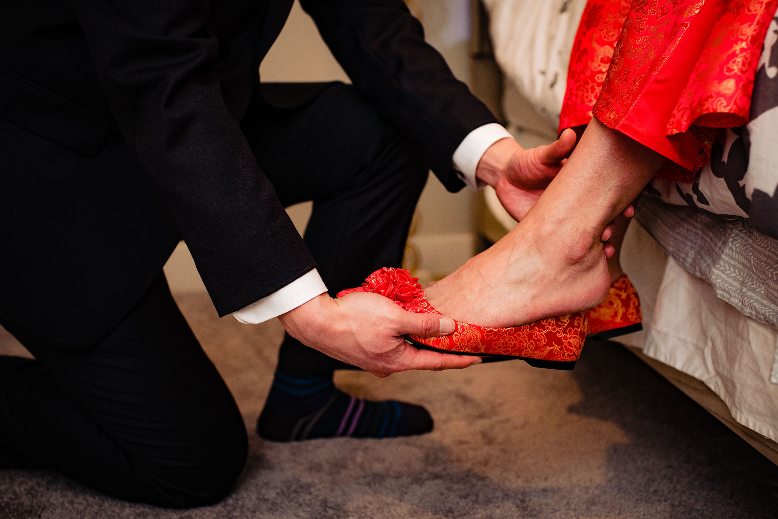 a groom putting on a bride's shoe for their calgary lake house wedding by calgary wedding photographer sean leblanc photography