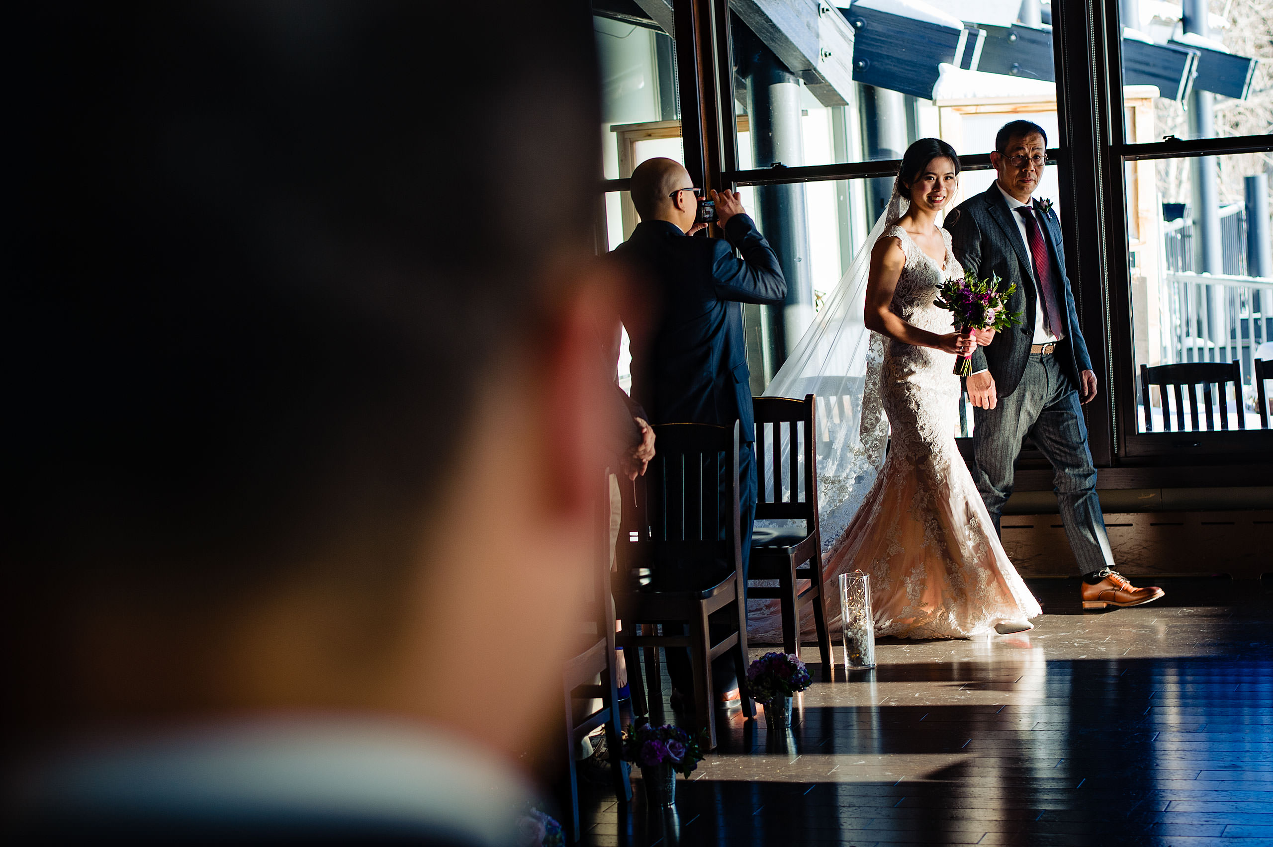 a bride being walked down the aisle by her dad for their calgary lake house wedding by calgary wedding photographer sean leblanc photography