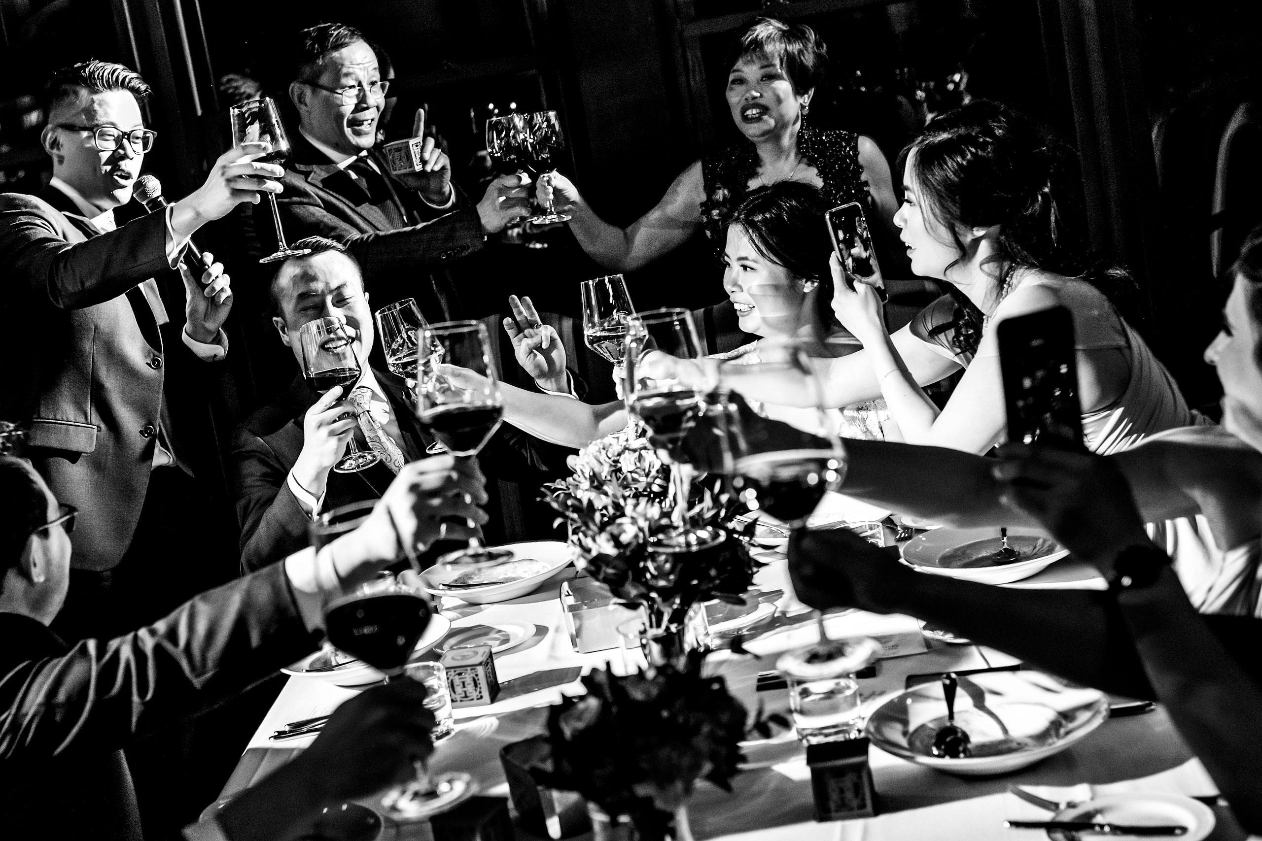 a group of people clinking glasses at a calgary lake house wedding by calgary wedding photographer sean leblanc photography