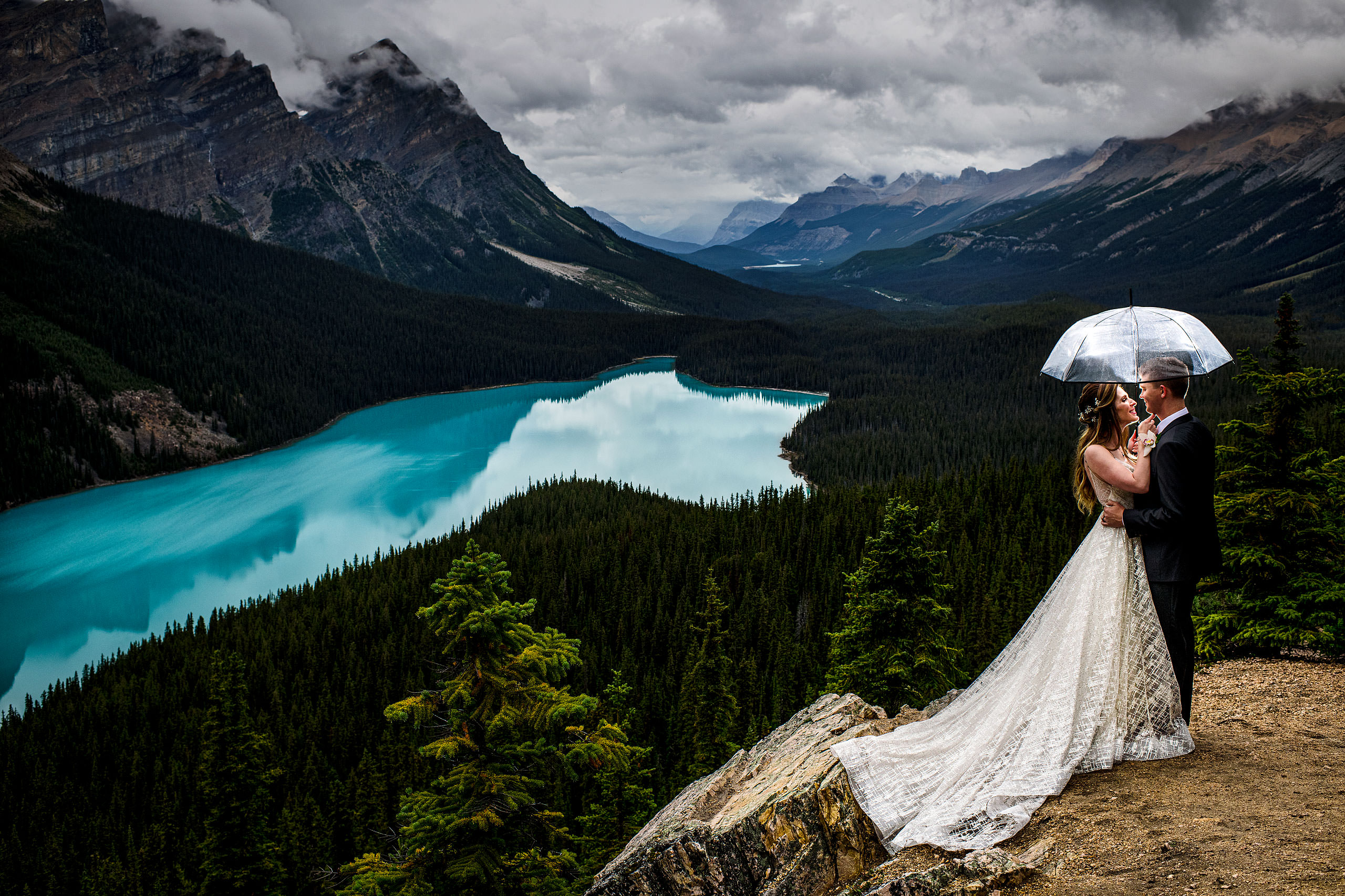 Bride and groom standing under an umbrella looking at each other by Peyto Lake by lake louise wedding photographer sean leblanc