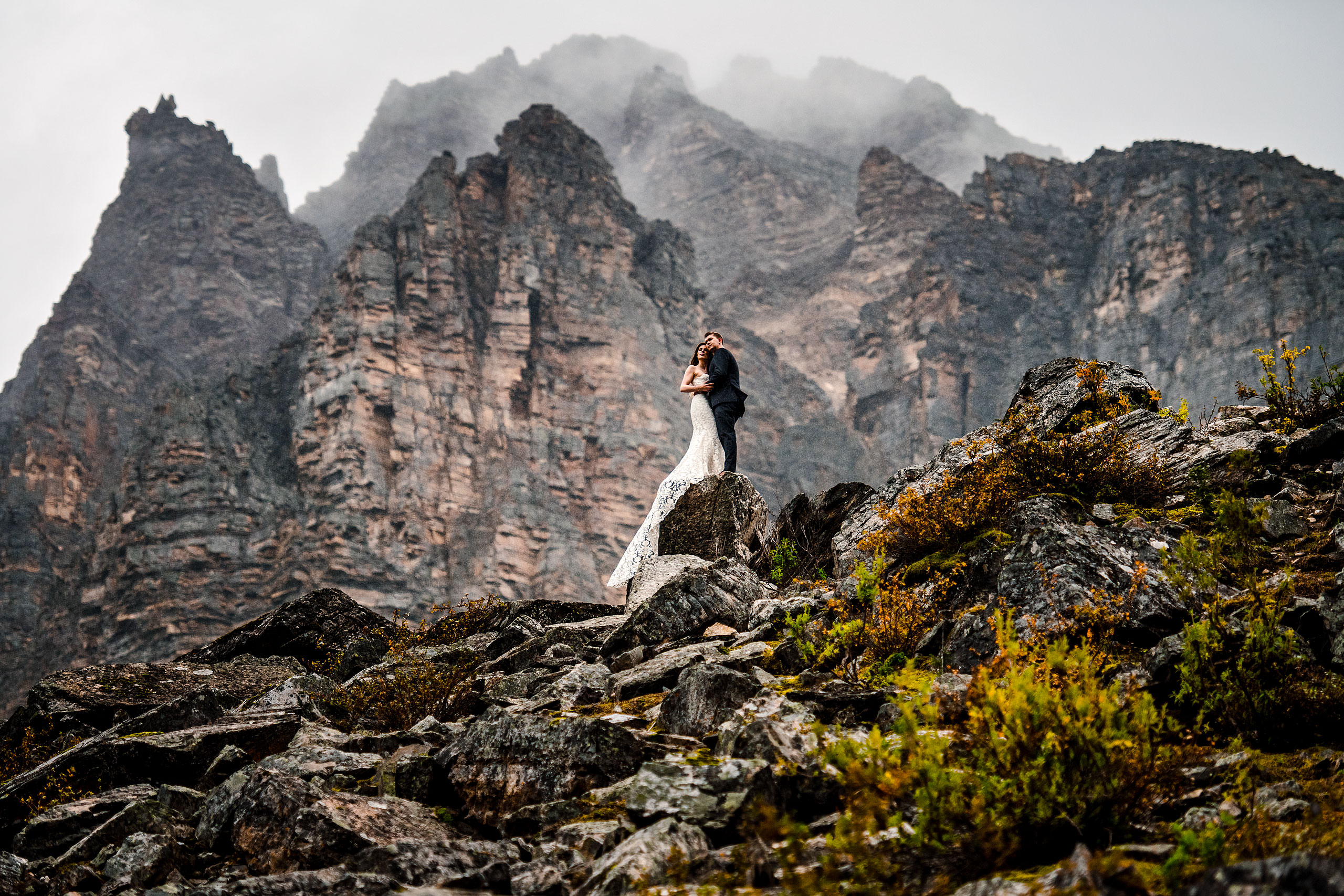 Bride and groom standing on a rock by moraine lake by lake louise wedding photographer sean leblanc