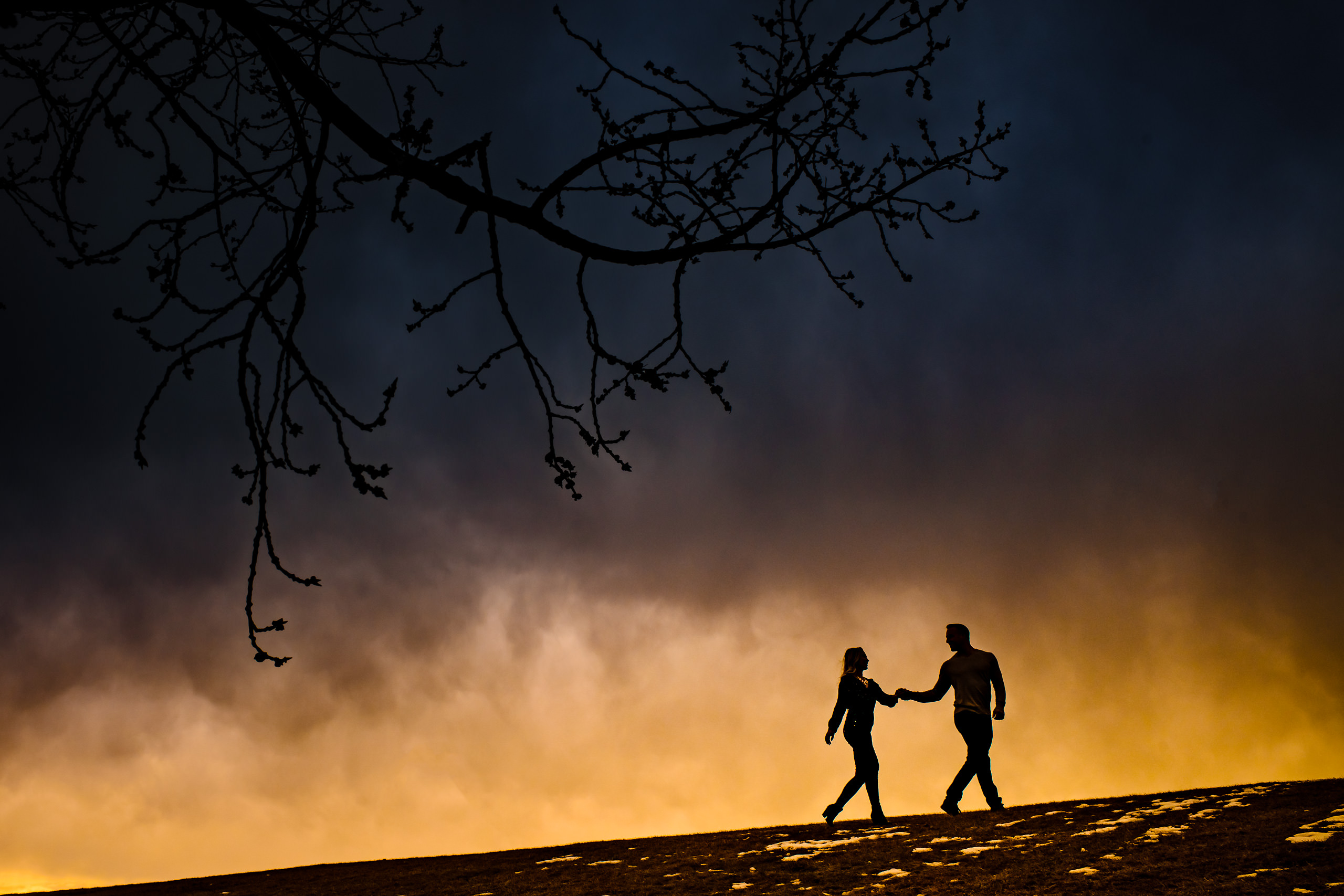 Man and a women walking along a hill top at sunset by calgary engagement photographer sean leblanc